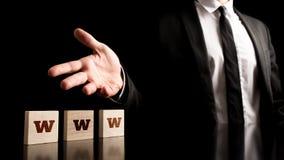 Hombre que representa pedazos de madera con las letras del WWW Fotografía de archivo
