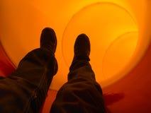 Hombre que resbala abajo a través de una diapositiva del tubo Foto de archivo