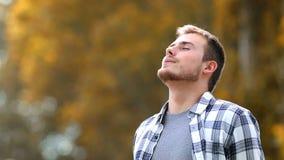 Hombre que respira en un parque en otoño almacen de metraje de vídeo