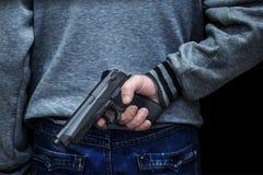 Hombre que retiene un arma detrás el suyo contra un fondo negro concepto de peligro, crimen fotografía de archivo