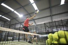 Hombre que rompe en la acción del tenis de la paleta Bolas de la cesta del entrenamiento en f Fotos de archivo libres de regalías
