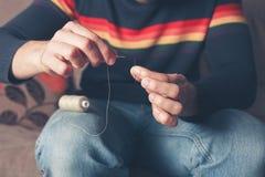 Hombre que rosca una aguja Imagenes de archivo