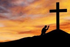 Hombre que ruega bajo cruz Fotografía de archivo