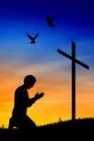 Hombre que ruega bajo cruz Fotografía de archivo libre de regalías