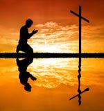 Hombre que ruega bajo cruz Imagen de archivo libre de regalías