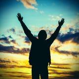 Hombre que ruega en fondo de la puesta del sol Imagen de archivo libre de regalías