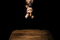 Hombre que ruega en la oscuridad en la tabla Fotos de archivo libres de regalías