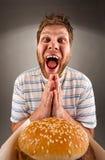 Hombre que ruega para los alimentos de preparación rápida Fotografía de archivo libre de regalías