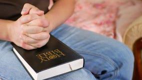 Hombre que ruega sosteniendo una Sagrada Biblia en casa metrajes