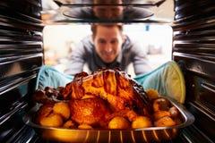 Hombre que saca la carne asada Turquía del horno Fotos de archivo