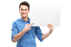 Hombre que señala en el cartel en blanco Imagenes de archivo