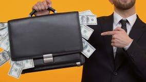 Hombre que señala en el dinero que se pega hacia fuera de su caso, renta adicional, capital metrajes