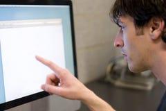 Hombre que señala en la pantalla de ordenador Foto de archivo libre de regalías