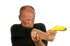 Hombre que señala su arma del plátano Imagen de archivo libre de regalías