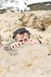 Hombre que se aferra a la roca. Imágenes de archivo libres de regalías
