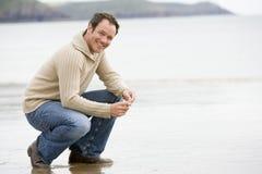 Hombre que se agacha en la playa Foto de archivo libre de regalías