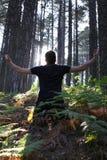 Hombre que se arrodilla con los brazos levantados en bosque Imagen de archivo