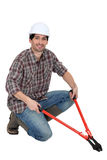 Hombre que se arrodilla con los perno-cortadores Imágenes de archivo libres de regalías