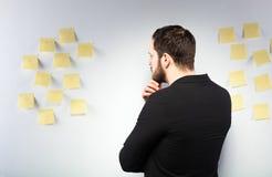 Hombre que se coloca al lado de una pared con los post-it Imagen de archivo libre de regalías