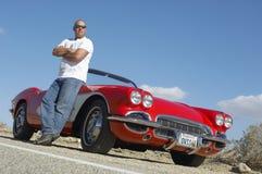 Hombre que se coloca al lado del coche clásico en el camino fotos de archivo