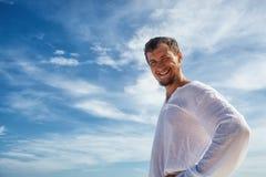 Hombre que se coloca antes de cielos azules con las nubes fotografía de archivo