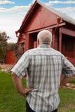 Hombre que se coloca cerca de casa roja Imagen de archivo