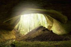 Hombre que se coloca cerca de la entrada enorme de la cueva Imagenes de archivo