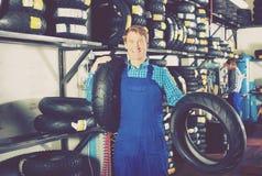 Hombre que se coloca con los neumáticos autos Fotos de archivo