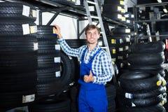 Hombre que se coloca con los neumáticos autos Imágenes de archivo libres de regalías