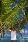Hombre que se coloca debajo de la palmera en la playa tropical Foto de archivo libre de regalías