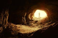 Hombre que se coloca delante de una entrada de la cueva Imágenes de archivo libres de regalías