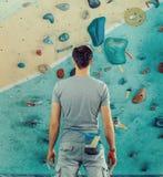 Hombre que se coloca delante de una pared que sube práctica Imagen de archivo libre de regalías