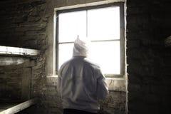 Hombre que se coloca delante de ventana en una cabina Foto de archivo libre de regalías