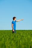 Hombre que se coloca en campo y señalar verdes Fotografía de archivo libre de regalías