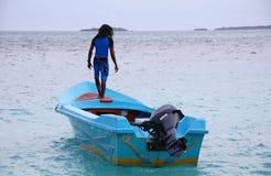 Hombre que se coloca en el barco de motor azul Maldivas Imágenes de archivo libres de regalías