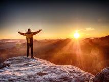 Hombre que se coloca en el borde rocoso Salida del sol de observación del hombre joven en el horizonte montañoso Imagen de archivo libre de regalías