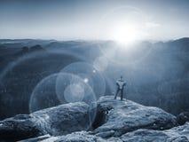 Hombre que se coloca en el borde rocoso Salida del sol de observación del hombre joven en el horizonte montañoso Fotos de archivo libres de regalías