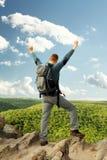 Hombre que se coloca en el top de la montaña Fotografía de archivo libre de regalías