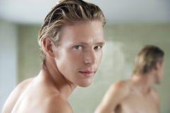 Hombre que se coloca en Front Of Bathroom Mirror Fotografía de archivo