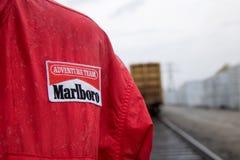 Hombre que se coloca en la lluvia que lleva el rainjacket de Marlboro imagenes de archivo