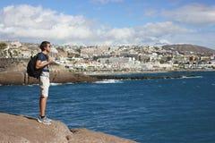 Hombre que se coloca en la montaña con la mochila imagen de archivo