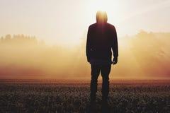 Hombre que se coloca en la niebla en la salida del sol Foto de archivo