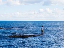 Hombre que se coloca en la pesca de las rocas Fotos de archivo