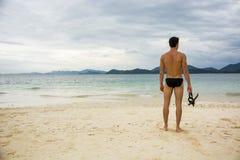 Hombre que se coloca en la playa Foto de archivo libre de regalías