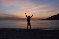 Hombre que se coloca en la playa en la puesta del sol imágenes de archivo libres de regalías