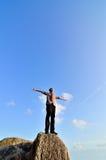 Hombre que se coloca en la roca Fotografía de archivo libre de regalías