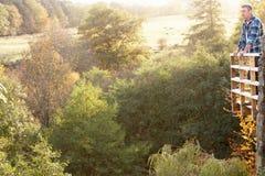 Hombre que se coloca en otoño de desatención del balcón de madera Imagen de archivo