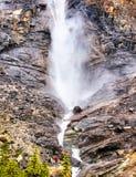 Hombre que se coloca en temor en la base de la cascada potente del rugido fotos de archivo