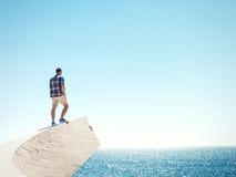 Hombre que se coloca en un acantilado y un mar imágenes de archivo libres de regalías