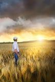 Hombre que se coloca en un campo del trigo Foto de archivo libre de regalías